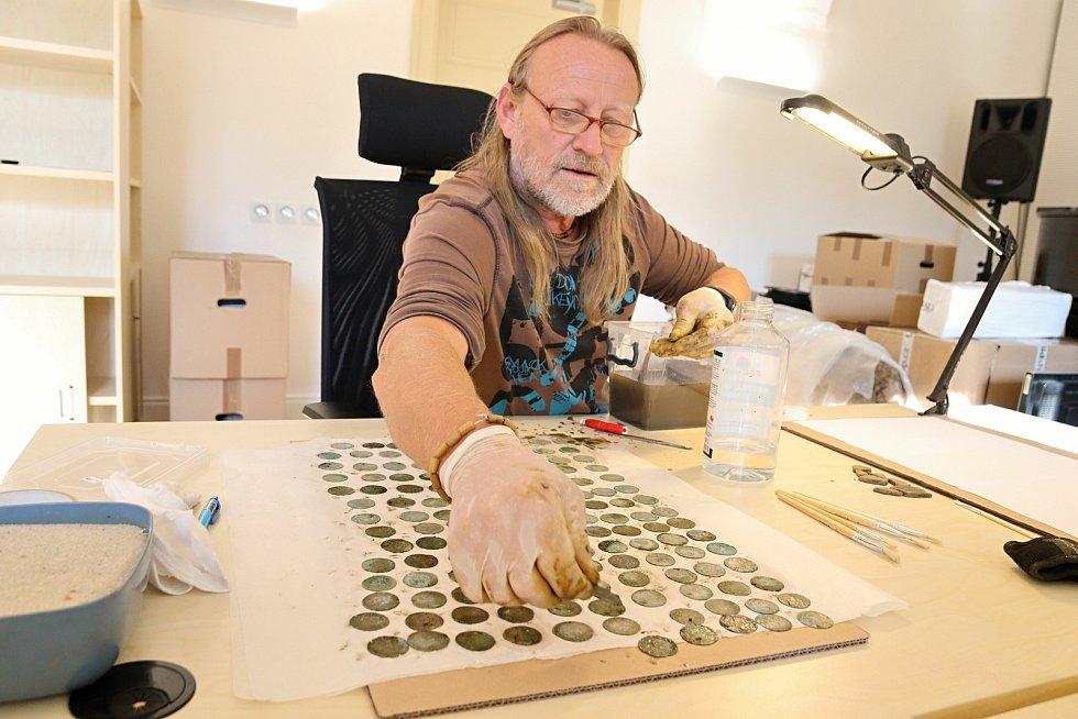 Konzervátor Muzea regionu Valašsko Zdeněk Hanáček zkoumá nález několika stovek stříbrných pražských grošů ze 14. století nalezených v lese v Ústí u Vsetína.