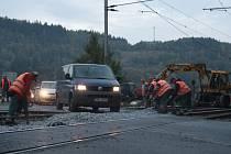 Dělníci opravují železniční přejezd před Bystřičkou.