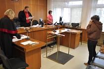 Martina Stavinohová, souzená za šíření poplašné zprávy, podvod, krádež a zneužití platební karty, skrývá tvář při hlavním líčení u Okresního soudu ve Vsetíně.