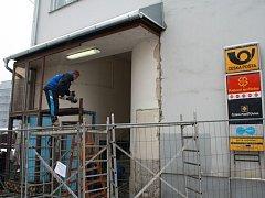 Pracovníci demontují vstupní dveře na poštu.