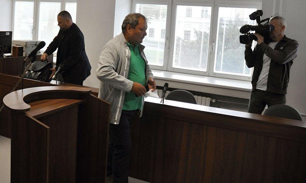 Obžalovaný Pavel Pryszcz z Karviné (v zeleném tričku) u Okresního soudu ve Vsetíně (úterý 10. září 2019). Obžaloba jej viní z obecného ohrožení z nedbalosti. V roce 2007 měl zanedbat opravu komína chaty Libušín, což mělo po letech (v roce 2014) za následe