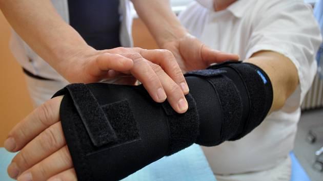 Znehybnění a zpevnění poraněného zápěstí pomocí ortézy.  Ilustrační foto.