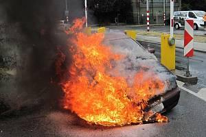Hasiči likvidují v pátek 19. července 2019 odpoledne požár osobního vozu Škoda před nákupním centrem ve Valašském Meziříčí.