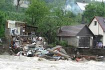 Rozvodněná Rožnovská Bečva podemlela ve Vidči menší domek, který se zřítil. Další dům je v ohrožení.