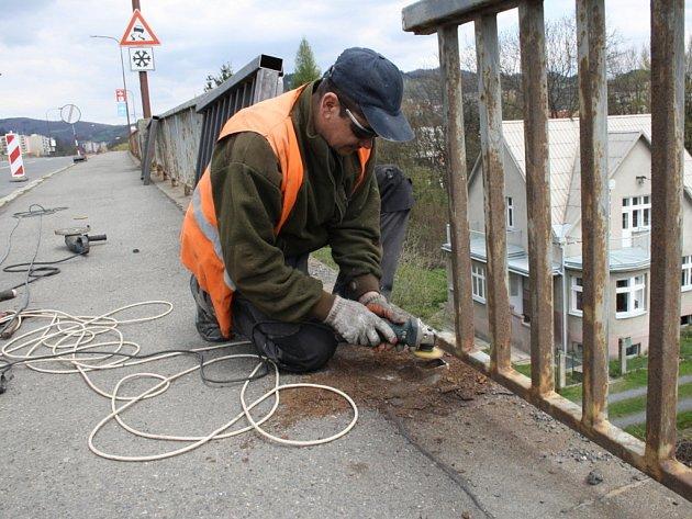 Pracovníci vyměnují staré prorezlé zábradlí za nové. Po skončení jejich práce nastoupí na jejich místo natěrači. Kvůli nedostatku peněz však letos mohou opravit jen jednu stranu mostu.