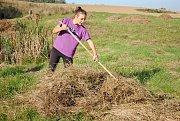 Studenti a ochránci přírody shrabují trávu.