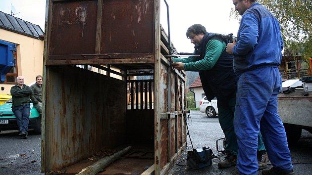 Řemeslníci Antonín Hajda (ve vestě) a Radek Machala (v modrém) z Ratiboře opravují v Oznici odchytovou klec na toulavého medvěda, který v posledních týdnech působí škody chovatelům na Valašsku a nebojí se přibližovat ani k lidským obydlím. Klec byla přive