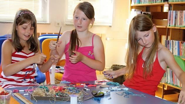 Děti vyrábějí pletené indiánské náramky v dětském oddlělení Masarykovy veřejné knihovny ve Vsetíně – Luhu; Vsetín, úterý 23. července 2013.
