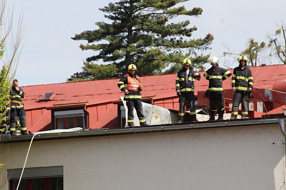 Hasiči zabezpečují střešní krytinu, kterou strhl silný vítr ze střechy Masarykova gymnázia ve Vsetíně ve středu 24. dubna 2019.