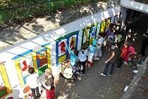 Děti z rožnovských základních škol malují barevný vláček do podchodu pod železniční tratí nedaleko vlakového nádraží v Rožnově pod Radhoštěm, pátek 19. září 2014.