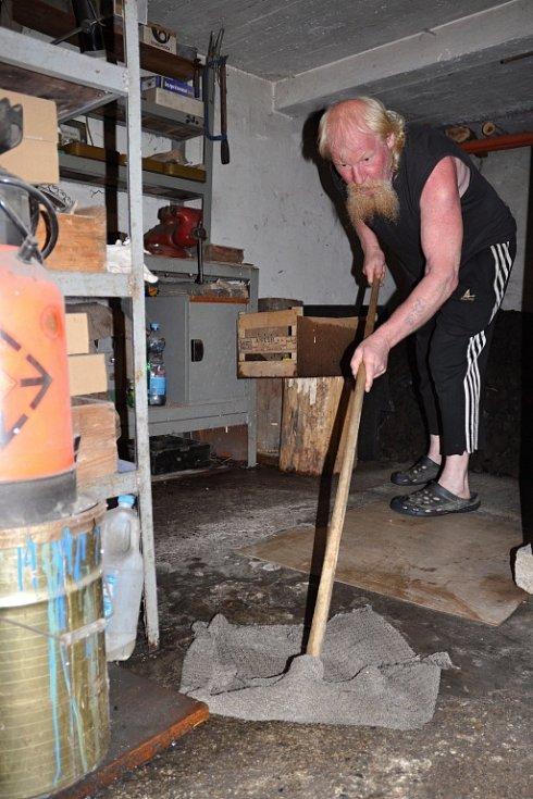 Ladislav Jelínek ze vsetínské místní části Semetín vyklízí v pondělí 1. srpna 2016 ráno sklep svého domu zatopený po silné bouřce a přívalovém dešti.