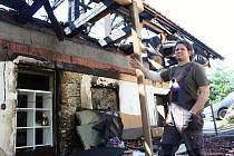 O velikonočním pondělí 2019 rodině Koudelových v Huslenkách doslova shořela střecha nad hlavou. Martin Koudela ukazuje následky požáru.