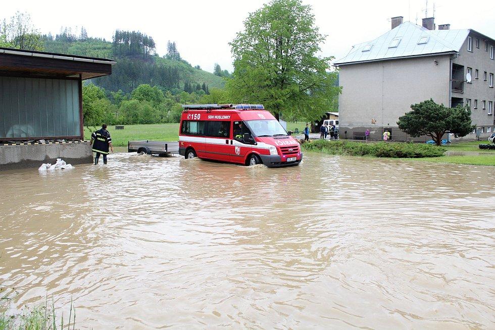 Velká voda potrápila hasiče v Huslenkách. Pod vodou byla část silnice, voda se rozlila do zahrad i za místní prodejnu.