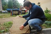 Archeolog Muzea regionu Valašsko Samuel Španihel ukazuje torzo pozdně barokního náhrobku nalezené při rekonstrukci kostela Nejsvětější Trojice ve Valašském Meziříčí; úterý 23. července 2019