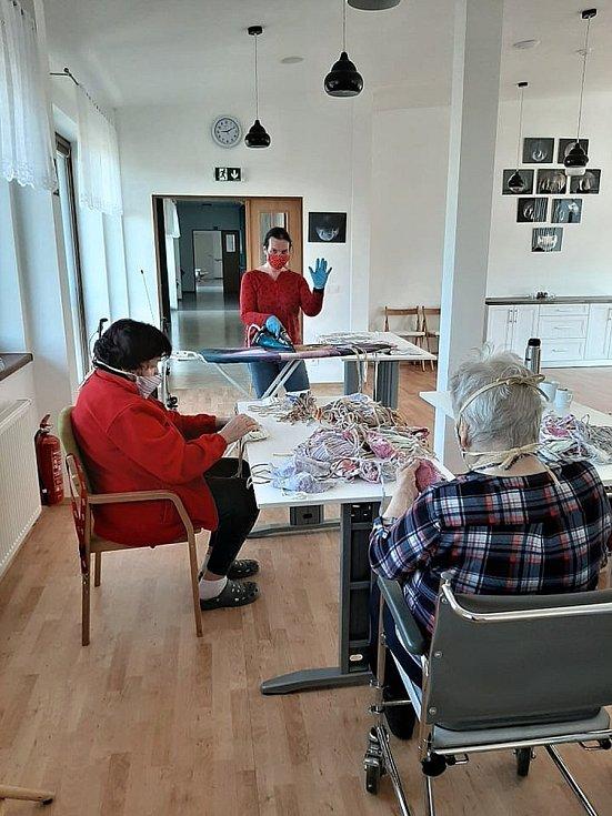 Pracovnice Diakonie Vsetín žehlí společně s klienty ochranné roušky v Domově Vyhlídka ve Vsetíně.