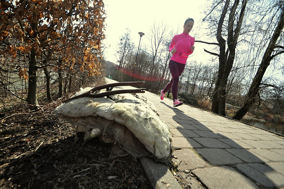 Kondiční běžkyně míjí jednu z hromad odpadu nashromážděného během akce Ukliďme Česko ve vsetínské Panské zahradě; sobota 27. března 2021