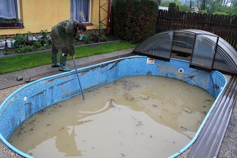 Obyvatelé Ústí u Vsetína likvidují 23. května 2019 následky velké vody. Miroslav Plášek loví nánosy z bazénu za domem.