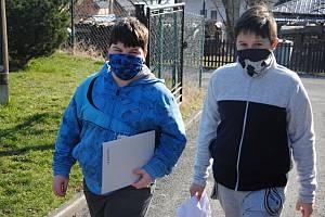 Kladerubští školáci Zdeněk Holáň (vlevo) a Petr Horák nesou do místní základní školy vypracované domácí úkoly. Zároveň si vyzvednou nové; středa 25. března 2020
