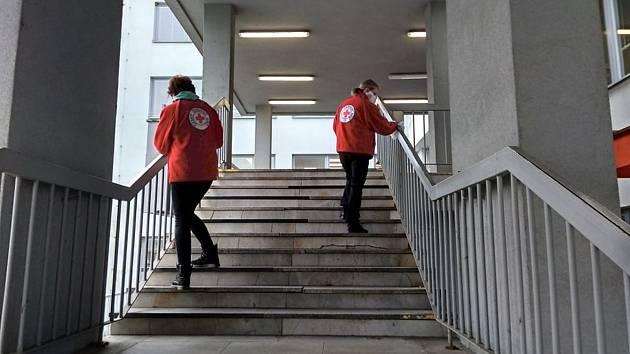 Členky vsetínské pobočky Českého červeného kříže dezinfikují zábradlí na schodišti do budovy polikliniky ve Vsetíně; říjen 2020