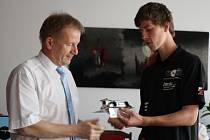 Ředitel školy Josef Slovák přebírá od týmového manažera Jaroslava Macka maketu soutěžního modelu formule 1.