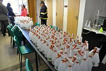 Dobrovolní hasiči obce Bystřička distribuují v neděli 15. března 2020 litrové lahve s dezinfekčním roztokem místním obyvatelům.