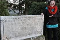 """Kamenná tumba. Jitka Cempírková z městského muzea ukazuje, že náhrobní deska v parku zámku  v Chotěboři už je pouhým torzem většího celku. Schází především velká váza z bílého mramoru s nápisem v němčině """"Mé vznešené milence""""."""