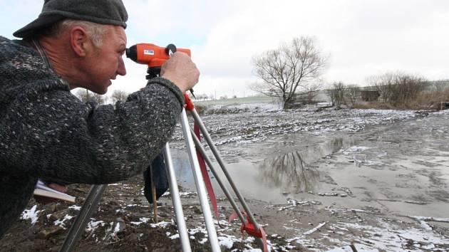Zeměměřič Miloslav Blažek nivelačním dalekohledem kontroluje, zda rybník Olšovec je už dostatečně hluboký.