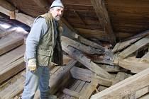 Stavební dělník František Nevrkla ukazuje zcela ztrouchnivělé trámy na půdě zámku ve Zboží, které byly dříve ukryty pod vrstvou betonu a nekvalitní izolace.