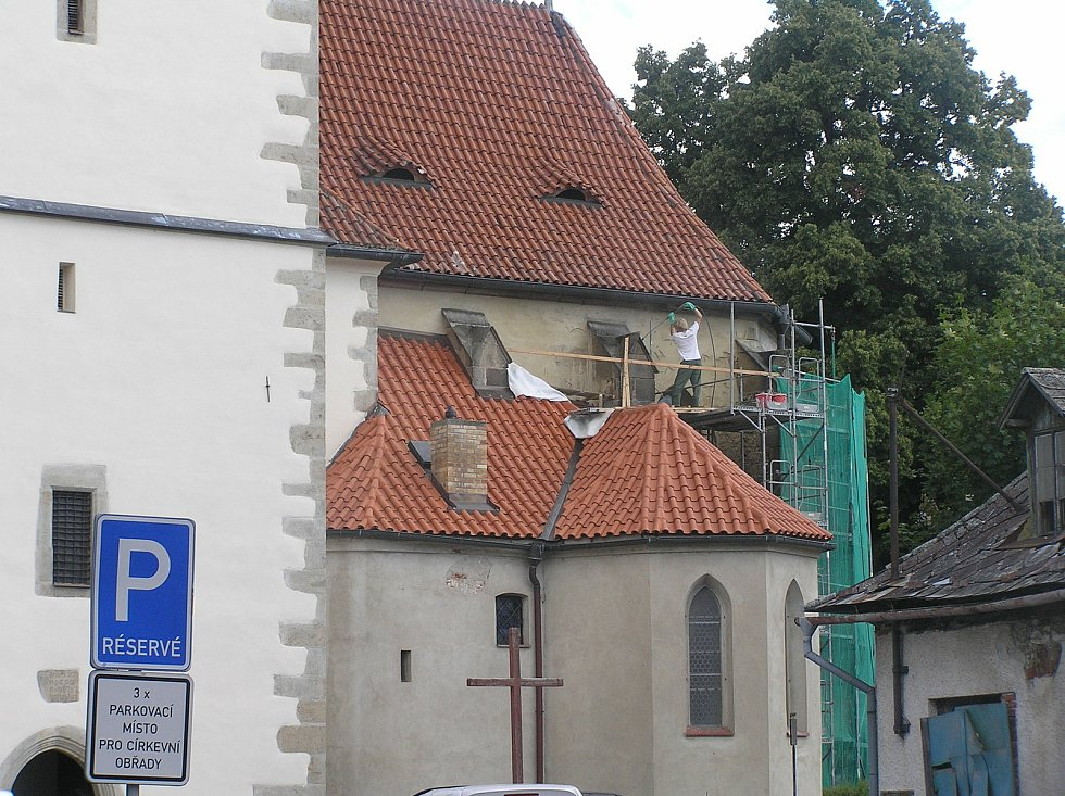 Na fasádě kostela v Ledči pracují dělníci. Náklady na opravy jdou do milionů.