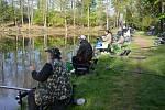 Břeh rybníku v zámeckém parku během závodů obsazený soutěžícími rybáři.