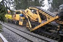 """Obří stroje nabírají kamení na trati Havl. Brod – Perknov. Materiál se proklepává a čistí, a poté je vrácen zpátky. Narýžovaná """"špína"""" – například písky nebo také zbytky uhlí – se dá posléze ještě využít."""