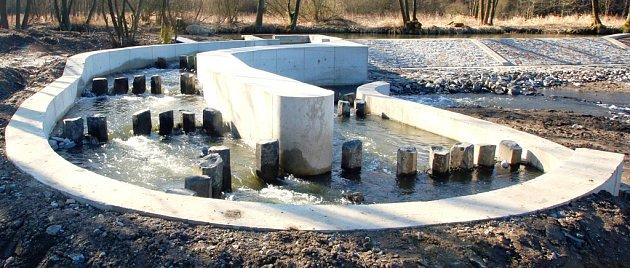 Obtokový kanál v řece Šlapanka umožní rybám a dalším vodním organismům obeplout jinak nezdolatelnou překážku – vysoký jez (na snímku vpravo), který vzdouvá řeku pro potřebu blízké vodní elektrárny.