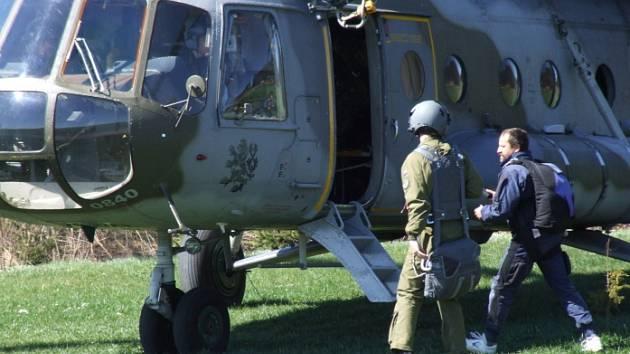 Padákový specialista letectva Milan Studený (vpravo) jako jeden z posledních nastupuje do vojenského vrtulníku.