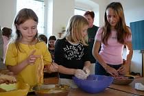 Obalí řízky na večeři. Dvanáct dětí se chystalo na Štědrý den ve škole opravdu poctivě. Samy si připravily večeři, zpívaly koledy a pak si předaly dárky.