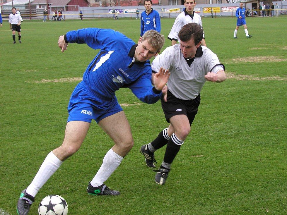 Momentka ze zápasu Ždírec - Žďár, který se hrál v dubnu 2003. Domácí Miroslav Kysilko (v modrém) si kryje míč před Markem Vomelou.