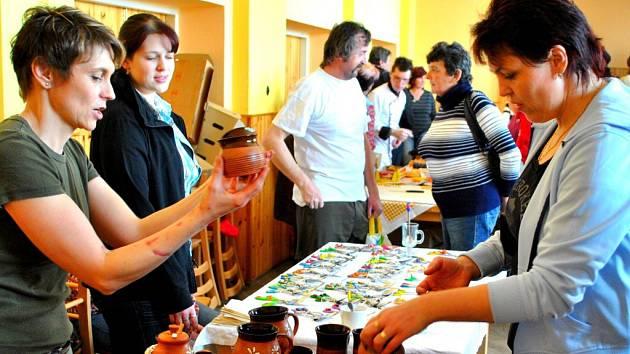 Keramička Lenka Sedláková (vlevo) pomalu ani nestačila všem zájemcům ukazovat nespočet nabízenách hrnečků, váziček, ozdobných květináčů nebo talířů a misek.  F