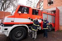 Přístavba hasičské zbrojnice byla nyní přerušena, ale krovy jsou před sněhem a deštěm dobře schovány. V nové garáži parkuje požární cisterna Praga. Za její volant usedají dva první muži sboru, jejich příjmení se rýmují - vlevo Janoušek, vpravo Hloušek.