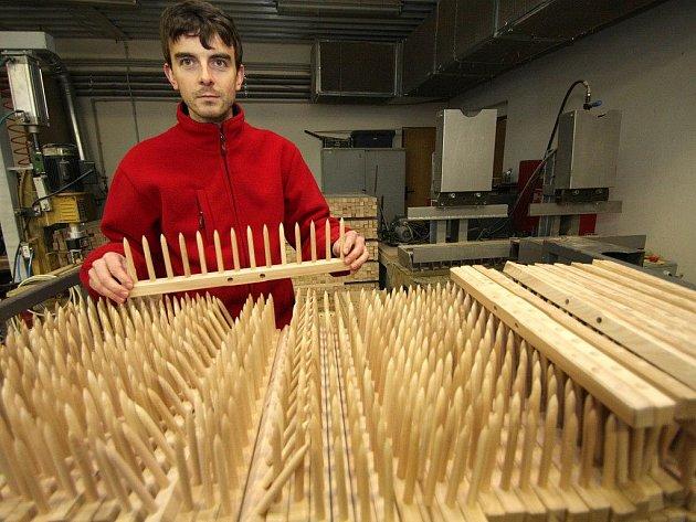 Obchodní ředitel firmy Petr Lidmila prohlíží hotové hřebeny na dřevěné hrábě.