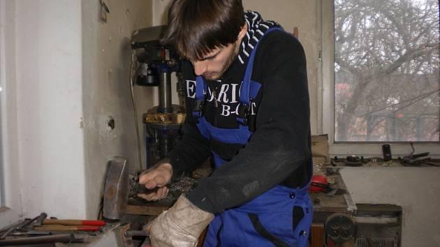 Kování pantu. Marek Šemík nejdříve  pant pořádně rozžhaví v plynové peci, poté ho může na bucharu ozdobně pokovat a ve finále ho zdobí takzvaným oblíkem (na snímku).
