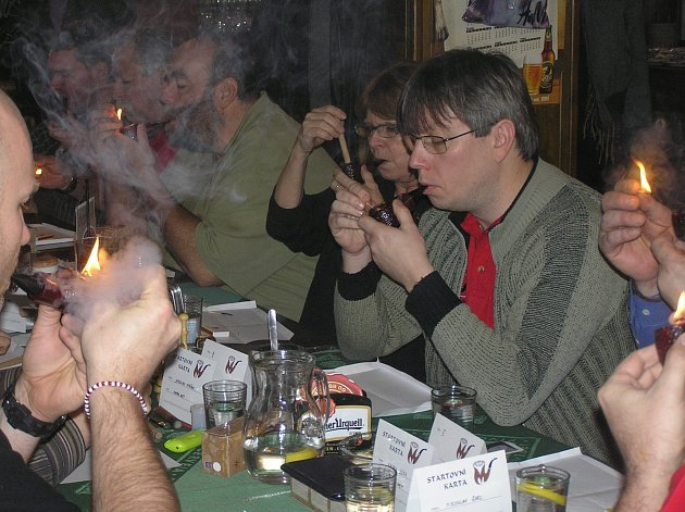 """KOUŘ HOUSTNE. Soutěž kuřáků dýmek se podobá odpolednímu  """"matiné"""" anglických lordů. Kuřák dýmky je noblesní, rozvážný, nehuláká, soutěžícím ženám se hlasitě tleská."""