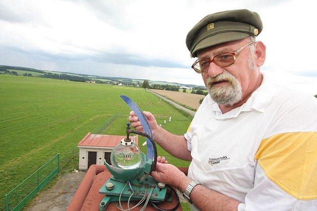 Heliograf na střeše meteorologické stanice v Hřišti registruje sluneční svit. Josef Šlezinger kontroluje papírový proužek, který byl přes kulovou čočku propálen slunečním paprskem.
