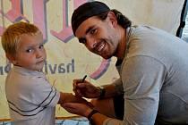 Na snímku se podepisuje na ruku malého fandy střední útočník HC Rebel, Lukáš Endál.