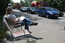 """Jako na pláži. Sluníčko a plážové sedačky, jen ten vzduch je o poznání méně čerstvý. Michaela Macourková zbrodské stavební školy pozoruje """"moře aut"""" na Masarykově ulici a zapisuje údaje."""
