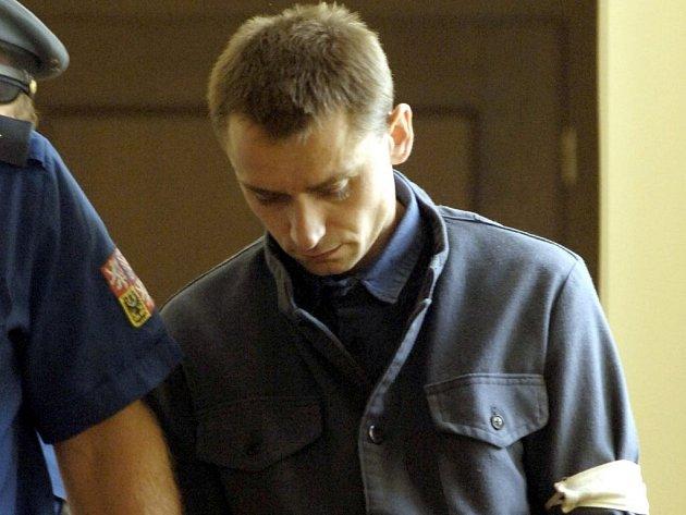 K soudu. Karel Caha přichází v doprovodu policistů k soudnímu jednání.