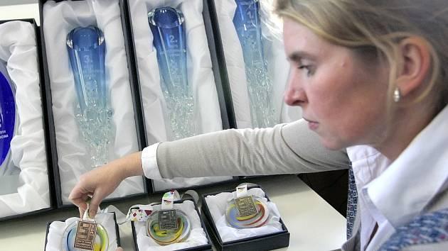Poháry a medaile. Krajská radní Jana Fialová si prohlíží medaile a poháry určené pro nejlepší mladé olympioniky.