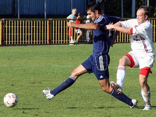 Meziříčský záložník Kamil Průša (vpravo) se pokouší zastavit útočníka Třebíče Jana Karáska v sobotním divizním derby, které Horácký fotbalový klub vyhrál na domácím hřišti 2:1.
