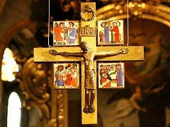 Těžký bronzový kříž nad kněžištěm farního kostela sv. Jakuba v Jihlavě s barevnými glazurami výjevů z evangelií.