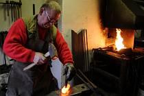 V kovárně. Jaroslav Dymák tráví ve své malé kovárně několik hodin, a to prakticky každý den. Těší ho každá kovářská práce. Skoro všechno, co ke svému řemeslu potřebuje, si vyková sám. Na snímku seká otvor do budoucího kladiva.