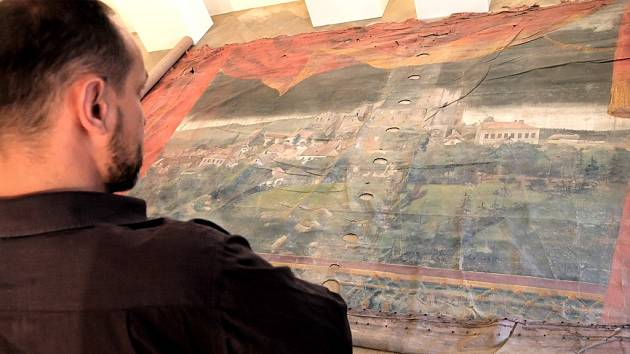Na oponě je zachycen pohled na obec a hrad po požáru v roce 1869. Na zadní straně je uveden nápis Ateliér Josefa Suchého Kolín, který oponu namaloval.