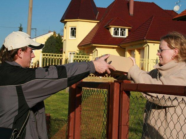 Brigádník Martin Ledvinka předává poštovní balík během rozvozu zásilek po Nové Vsi u Chotěboře. V pátek jich měl v autě šestadvacet.